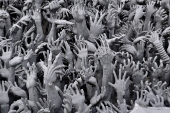 Hands clawing their way to the surface at Wat Rong Khun