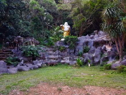 Phra Sang-Krachai Buddha statue amongst the lush vegetation and animal statues.
